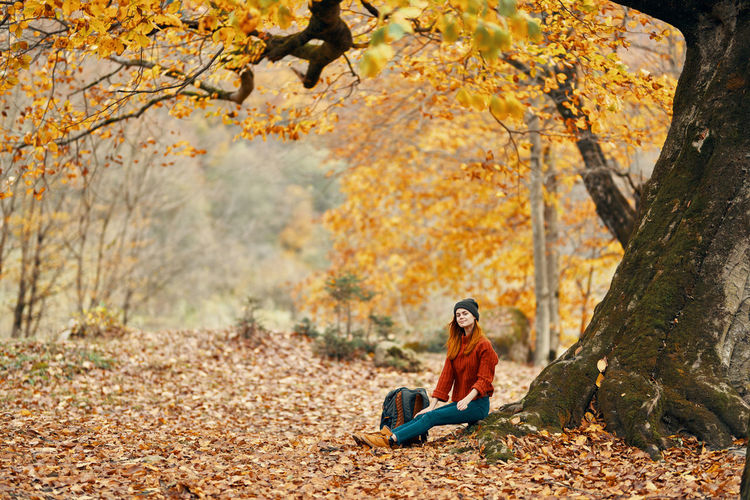 Young woman sitting on land in autumn