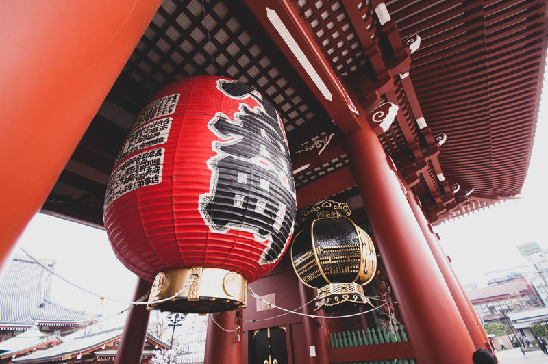 Low angle view of lanterns hanging by building