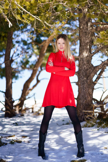 Full length of young woman against red tree