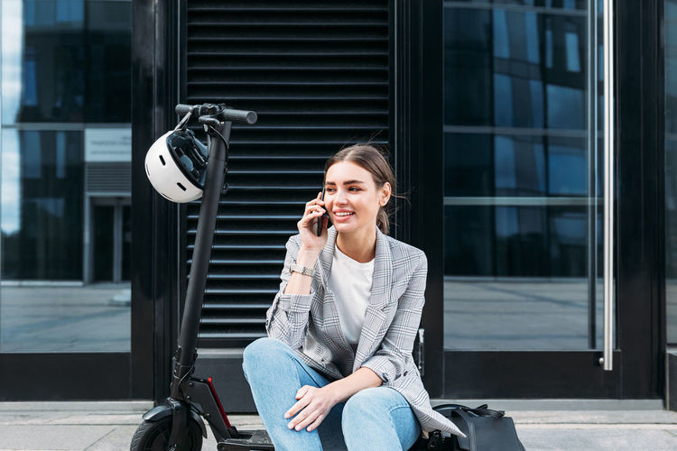 Young woman sitting on seat in city