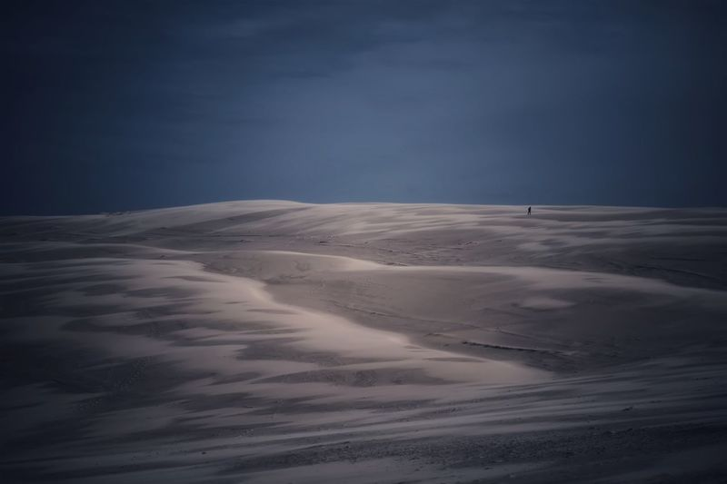Scenic view of desert land against sky during winter