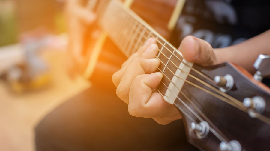 Acoustic Guitar Artist Arts Culture And Entertainment Finger Guitar Hand Holding Human Body Part Human Hand Midsection Music Musical Equipment Musical Instrument Musician One Person Playing Plucking An Instrument Skill  String Instrument