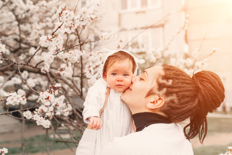 Beautiful adorable baby with her mother at the spring flowers blossom background. Mom and daughter love Togetherness Bonding Emotion Tree Portrait Women Childhood Child Happiness Plant Smiling Young Women Family With One Child Nature Family Focus On Foreground Flower Love Springtime Hair Positive Emotion Outdoors Love Mother And Daughter Mother And Son