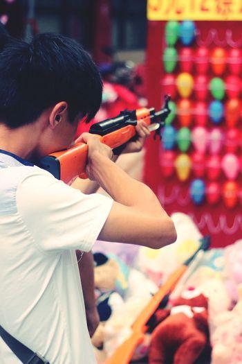 Boy shooting with gun at balloons in amusement park