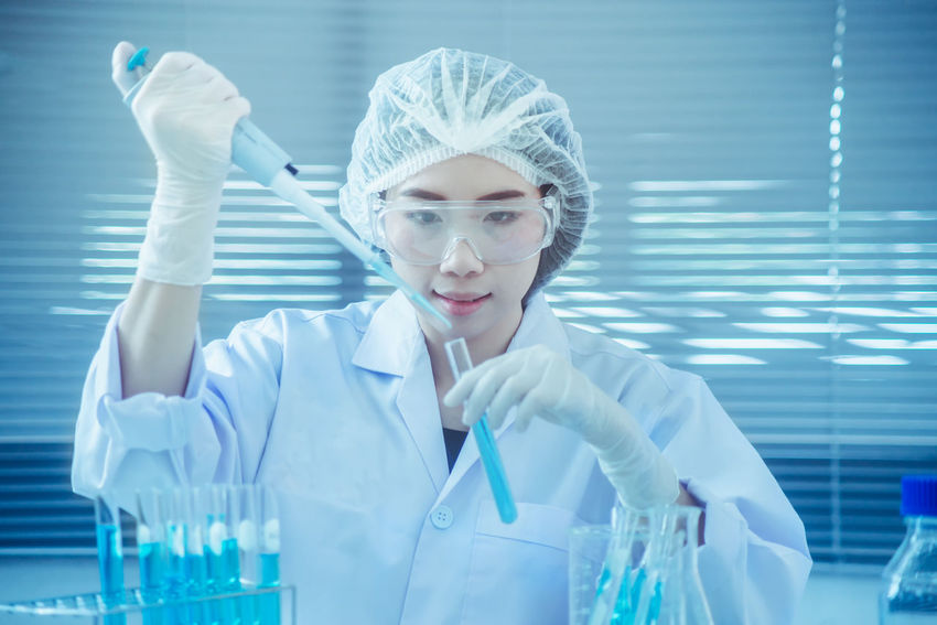 Biotechnology Clothing Education Front View Healthcare And Medicine Holding Indoors  Lab Coat Laboratory Occupation One Person Portrait Protection Protective Eyewear Research Science Scientific Experiment Scientist Skill  Surgical Cap Surgical Glove Women Young Adult