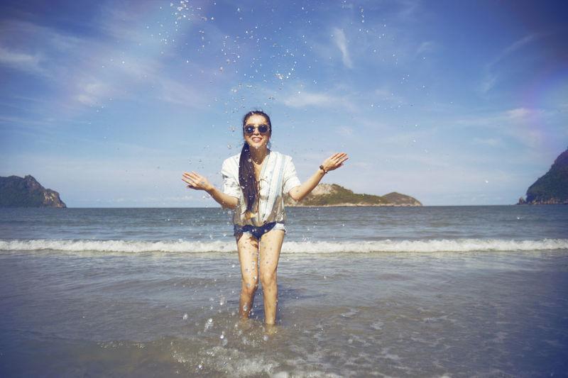 Portrait of woman wearing sunglasses splashing water in sea