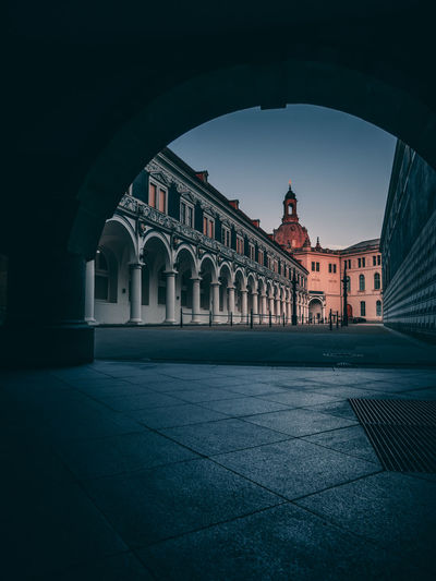 Historic Building Seen Through Arch In City During Sunset