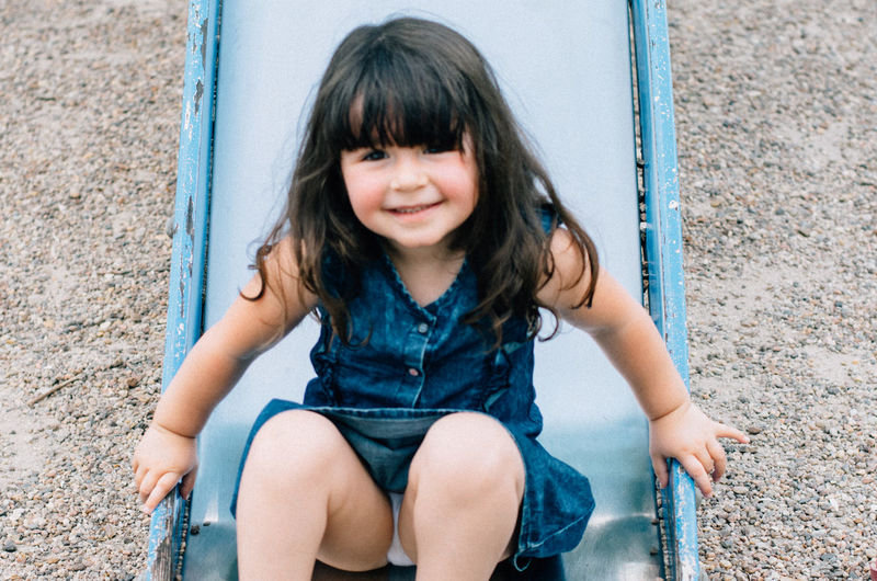Portrait of smiling girl playing on slide
