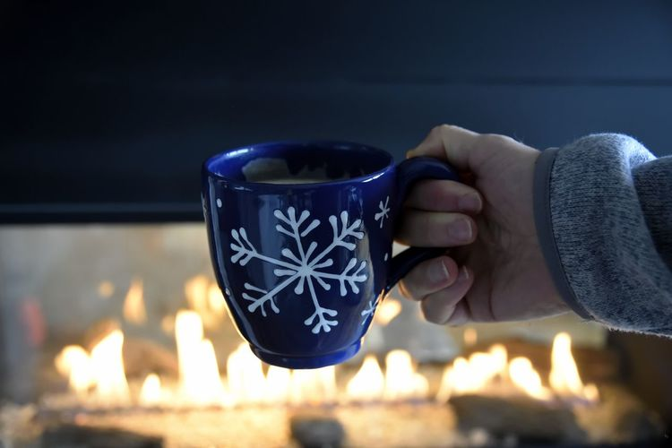 Cropped image of woman holding coffee cup against fireplace