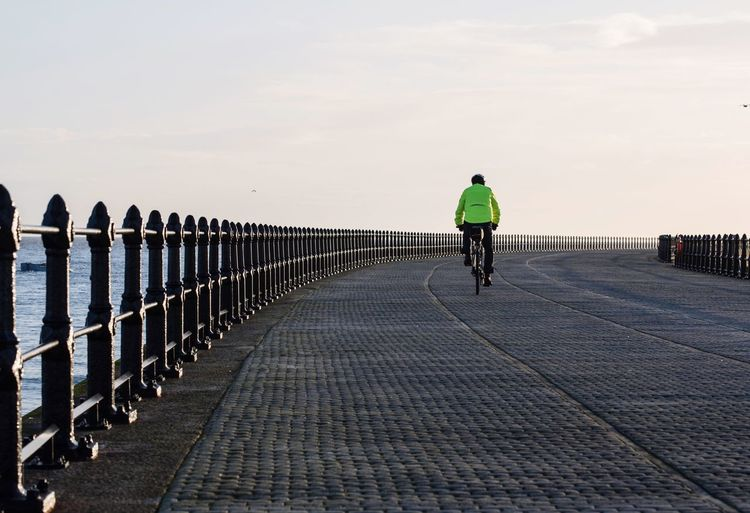 Rear View Of Man Riding Bicycle On Bridge By Sea Against Sky