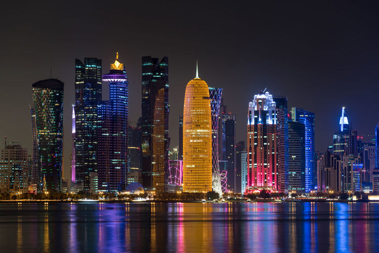 Doha skyscraper illuminated at night, Qatar, Middle East. Building Exterior Architecture Night Built Structure Illuminated Building City Office Building Exterior Skyscraper Water Waterfront Cityscape Landscape Urban Skyline Sky Tall - High Reflection Modern No People Financial District  Doha Qatar Middle East ASIA