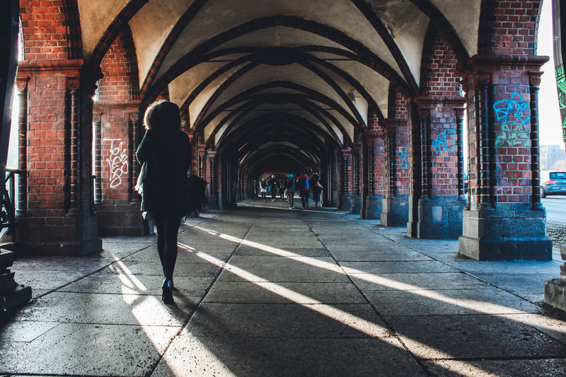 Rear View Of Woman Walking In Colonnade