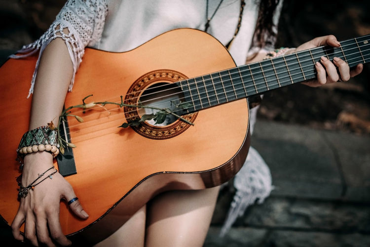 Cropped figure of hippie woman with boho wood beaded bracelets holding a guitar