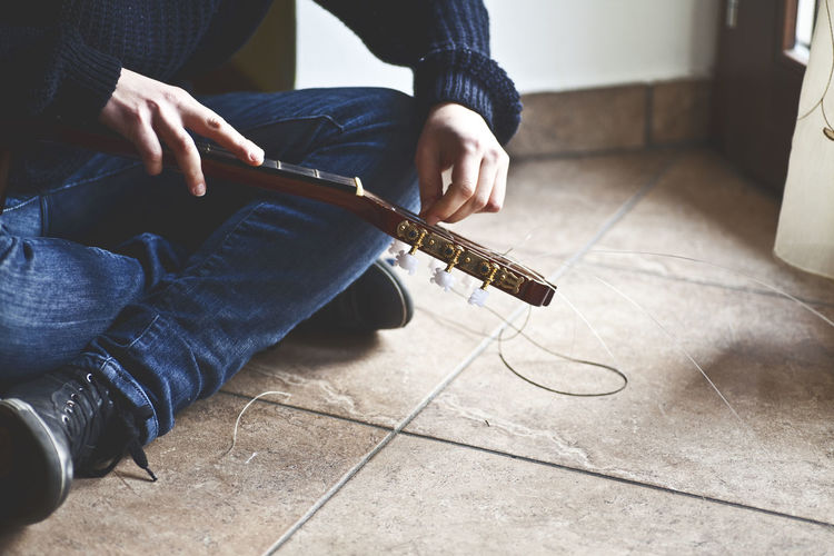 Arts Culture And Entertainment Cable Day Electric Guitar Guitar Human Hand Indoors  Lifestyles Low Section Music Musical Instrument Musical Instrument String Musician One Person People Playing Plucking An Instrument Real People Sitting Skill  Technology
