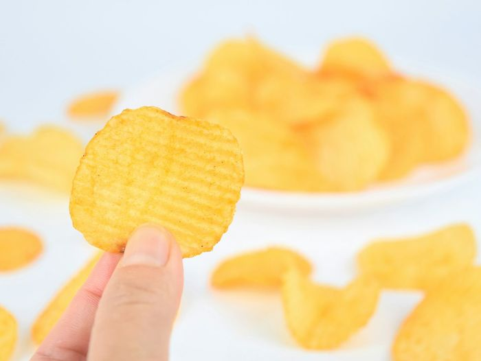 Potatoe chips in hand Human Hand Human Body Part One Person Holding Food And Drink Food Indoors  Yellow Close-up Lifestyles Macro Unhealthy Snacktime Ready-to-eat Potato Chip Indoors  Holding In Hand Eating