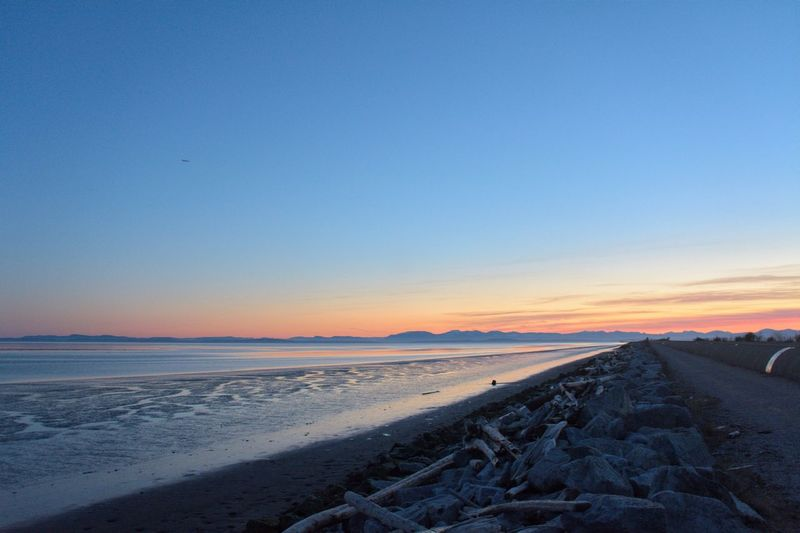 Sky Scenics - Nature Beauty In Nature Sea Land Water Sunset Horizon Horizon Over Water Blue Idyllic Winter Tranquility Tranquil Scene Sand Beach Nature No People Clear Sky