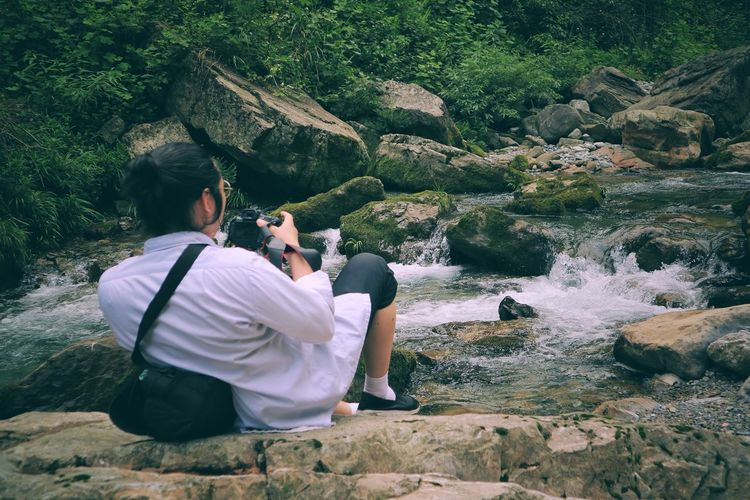 Rear view of man photographing stream in forest