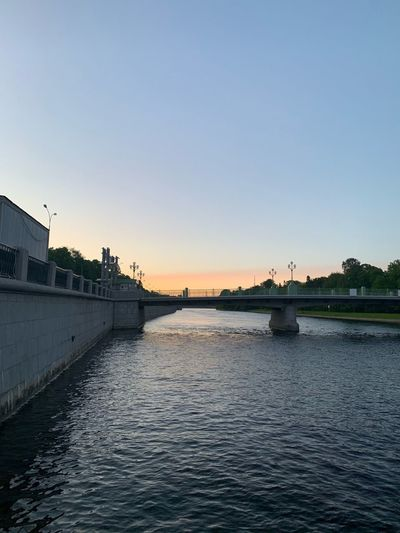 Bridge over river against clear sky during sunset