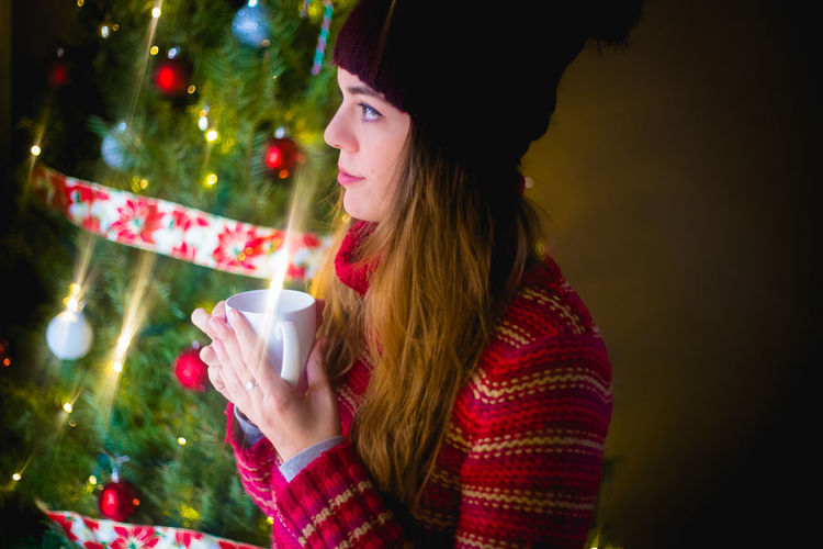 Midsection of a woman drinking water from christmas tree
