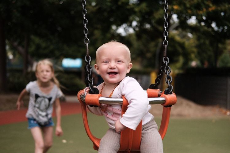 Childhood Baby Happiness Fun Playing Playground Swing Casual Clothing Focus On Foreground Smiling Two People Real People Hanging Togetherness Outdoors Leisure Activity Girls Cheerful Outdoor Play Equipment Day