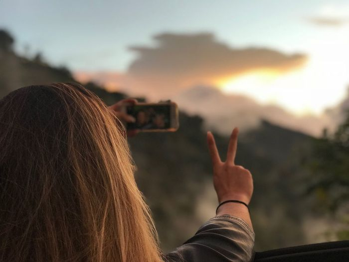 Rear View Of Woman Gesturing Peace Sign While Taking Selfie Against Sky