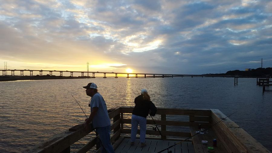 Man and woman on pier fishing in sea at sunset