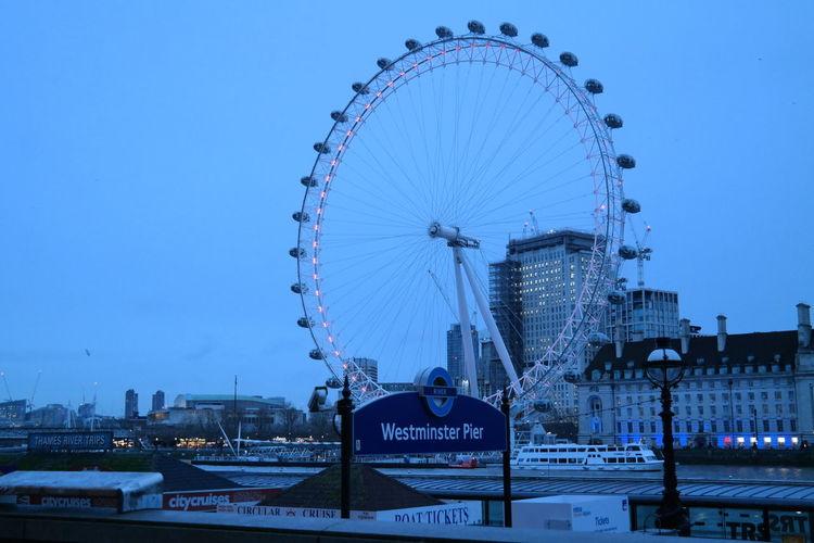 Ferris wheel in city against blue sky