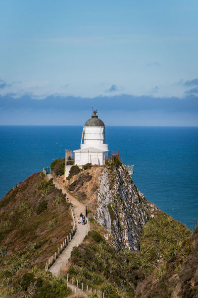 the lighthouse of nugget point on a sunny day with blue sky Nugget Point Lighthouse Path Architecture Beauty In Nature Building Building Exterior Built Structure Cloud - Sky Day Direction Hill Horizon Horizon Over Water Lighthouse Nature New Zealand No People Outdoors Pacific Ocean Scenics - Nature Sea Sky Tower Water The Architect - 2018 EyeEm Awards