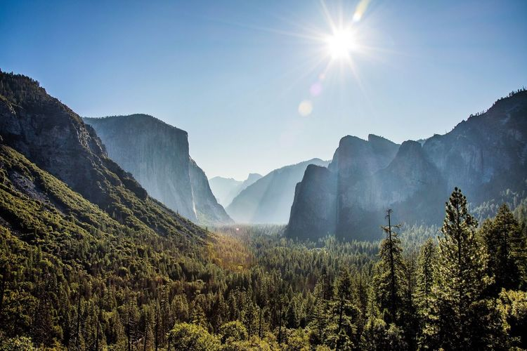 Scenic view of mountains against bright sun in yosemite national park