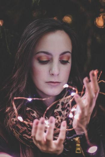 Close-Up Of Beautiful Woman Holding Illuminated Lights