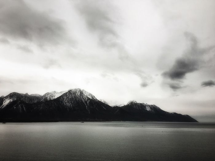 Scenic view of lake geneva by mountains against sky