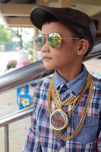 Close-Up Of Boy Wearing Sunglasses And Gold Chains By Railing