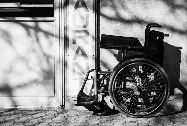 Wheelchair on cobblestone street by wall