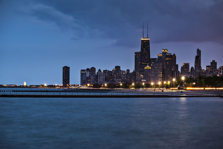 Illuminated city and river at dusk