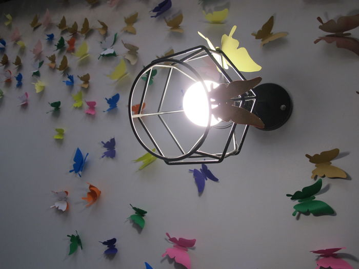 Low angle view of illuminated lighting equipment hanging on wall