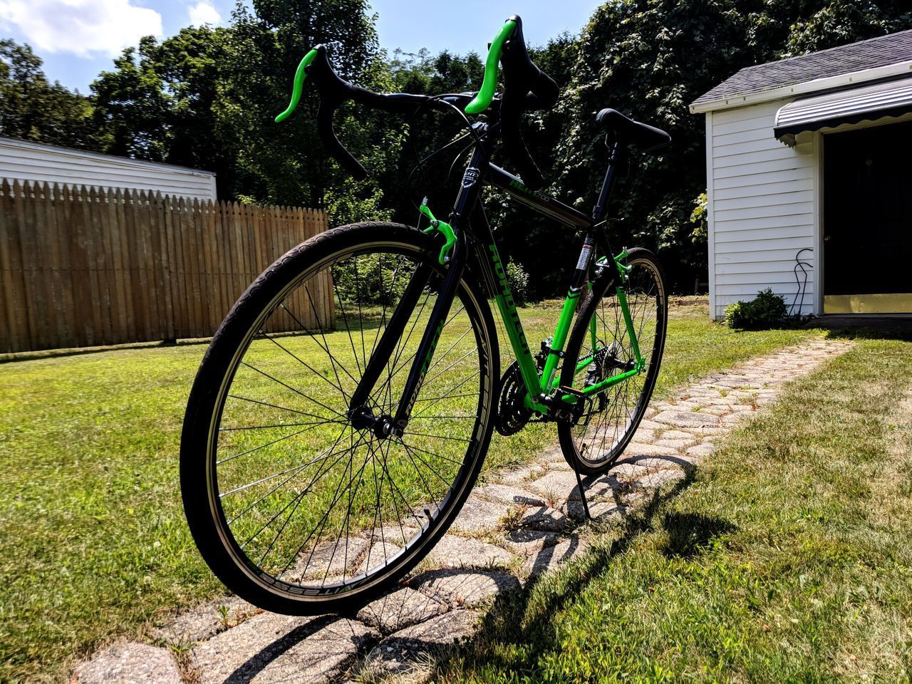 bicycle, plant, grass, land vehicle, transportation, built structure, mode of transportation, building exterior, architecture, nature, tree, day, no people, field, stationary, green color, parking, building, growth, outdoors, wheel