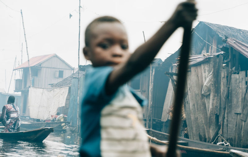 A boy in a boat Makoko Architecture Boys Building Exterior Built Structure Child Childhood Day Leisure Activity Lifestyles Males  Men Nautical Vessel One Person Outdoors Real People Selective Focus Transportation Waist Up Water