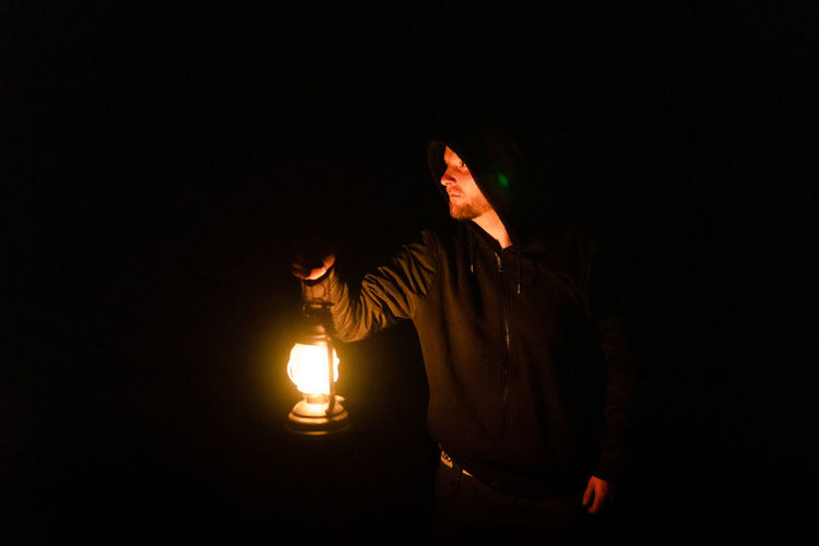 Midsection of man with illuminated lighting equipment against black background