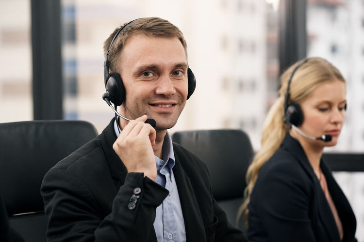 Portrait of smiling man wearing headset by colleague in call center