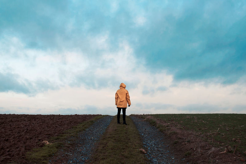 Man standing on road against cloudy sky