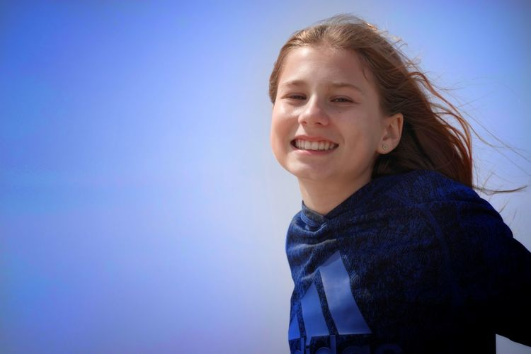 Portrait of a smiling girl against blue sky
