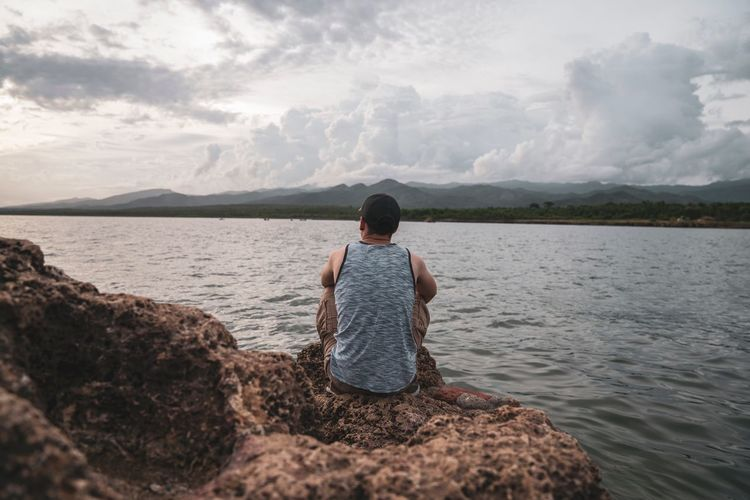 Contemplate Water Rear View One Person Sky Beauty In Nature Real People The Portraitist - 2018 EyeEm Awards Women Tranquility Beach Vacations Mountain Nature Day Cloud - Sky Scenics - Nature Outdoors Lifestyles Leisure Activity Lake Looking At View