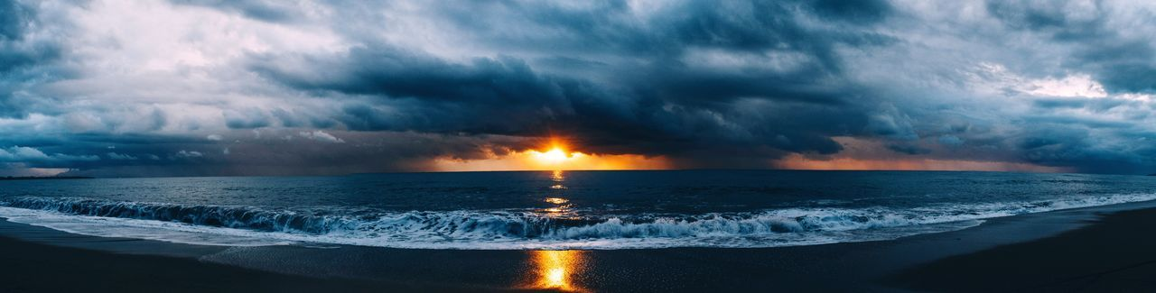 Panoramic view of beach against cloudy sky at sunset