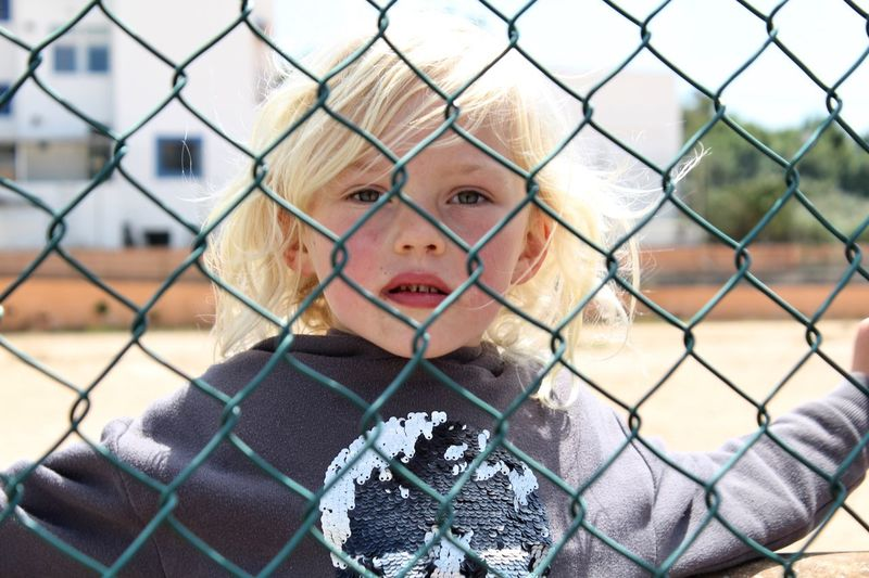 Portrait of boy seen through chainlink fence