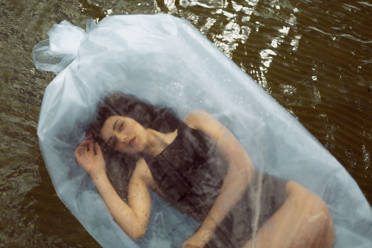 High angle view of woman lying down in water