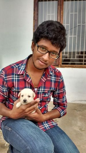 Portrait Of Young Man Holding Puppy While Crouching Against House