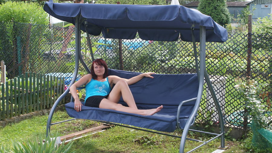 Young woman relaxing on swing in yard