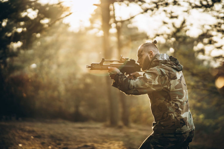 Side view of army soldier aiming gun in forest