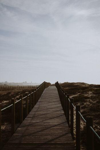 Boardwalk amidst landscape against sky
