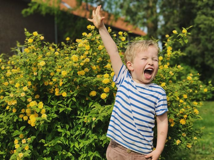 Happy Boy Screaming While Standing Against Plants